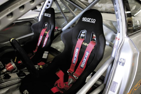 Inside, the roll cage surrounds a pair of Sparco pro2000 race seats with matching harnesses. The driver inputs are made with a Sparco steering wheel and a Wilwood pedal assembly with a matching E-Brake controller.